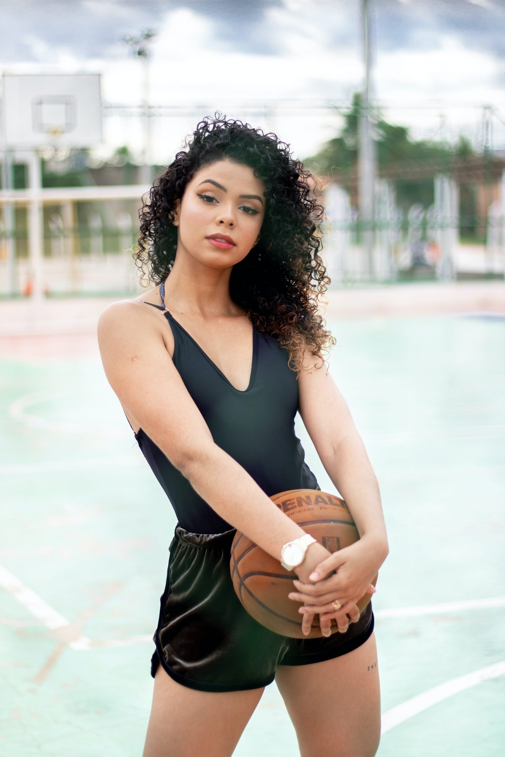 woman-with-curly-hair-extensions-holding-basketball