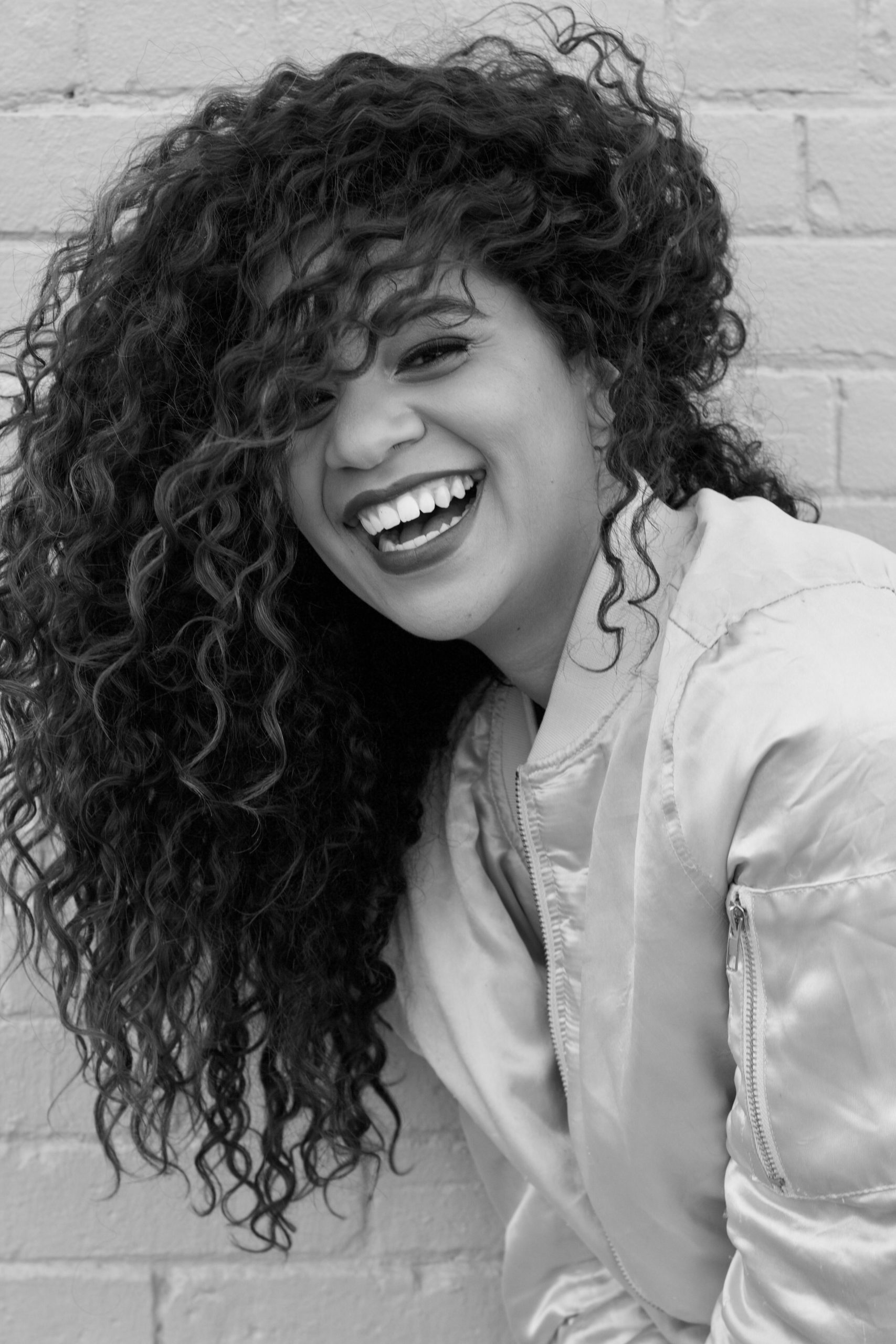 Woman-Laughing-With-Loose-Curls-Human-Hair-Extensions